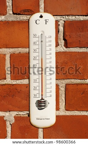 A photo an outdoor thermometer on brick wall