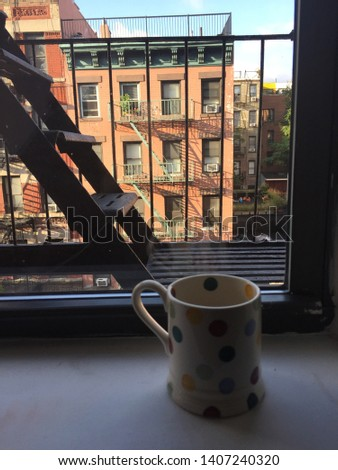 A photo from a New York apartment, sitting on the window sill is a spotty mug of tea. Outside the window is a black fire escape which looks over a block of apartments on the other side of the road.
