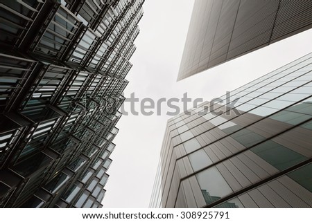 A photo looking up capturing three different buildings on an angle on a foggy day #308925791