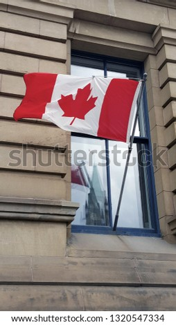 A photo of a Canadian Flag in a window of the Office of the Prime Minister and Privy Council building on Wellington St. Ottawa, ON, CAN. A reflection of the Peace tower clock is in the window as well.