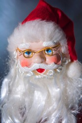 A photo of a Christmas tree ornament in the form of a Santa's head. Picture are modeled on a portrait photo style.