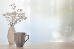 A photo of a desk with a white vase with dried white flowers and a gray cup with coffee on a background of sun-lit curtains. Copy space