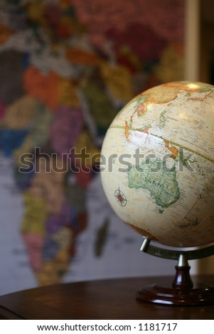 A photo of a globe on a desk with a map in the background