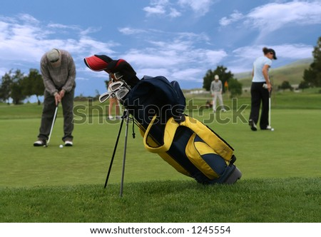 A photo of a golf club bag with golfers in the background (Focus on Golf Bag)