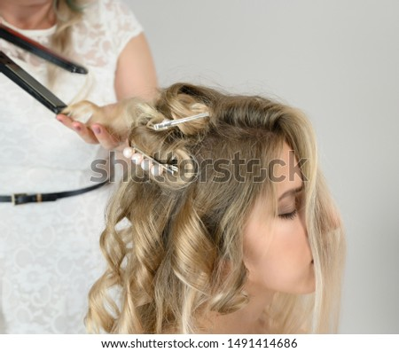 A photo of a hairdresser working on a model's hair in a studio. Makes a hairstyle, styling hair on a white background.
