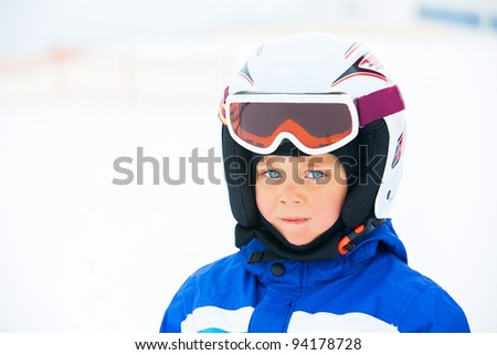 A photo of a Junior skier. Little cute boy with skis and a ski outfit