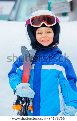 A photo of a Junior skier. Little cute boy with skis and a ski outfit. Vertical view
