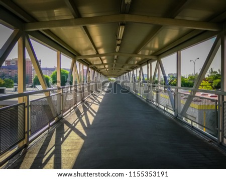 A photo of a long pedestrian walkway in a bridge with sunlight on the left and shadows on the right, made of metallic triangular structure, connects the Chamartin railway train station with the street #1155353191