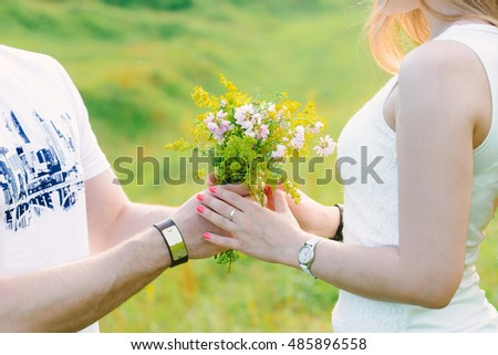 A photo of a man presenting a cute wildflowers bouquet to his girl, romantic, green background #485896558