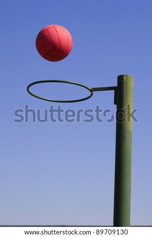 A photo of a red netball falling through a green hoop, with blue sky background