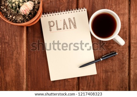 A photo of a spiral notepad with the word Plan, with a cup of coffee and a blooming cactus plant, shot from the top on a dark rustic wooden desk with copy space, a planning mockup