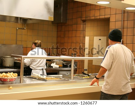 A photo of a teenager waiting for food at a cafeteria