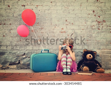 A photo of a vintage child taking a picture with an old camera against a brick wall with balloons and a teddy bear for a creativity or vision concept.