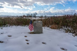 A photo of an American flag beside a headstone on the Gettysburg National Military Park on the field of Pickett's Charge in Pennsylvania where union and confederate soldiers battled in July of 1863.
