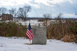 A photo of an American flag beside a headstone on the Gettysburg National Military Park on the field of Pickett's Charge where union and confederate soldiers battled in July of 1863.