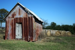 A photo of an old rusty shed next to bales of hay.