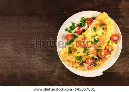 A photo of an omelette with cherry tomatoes, parsley. and grated cheese, shot from above on a rustic wooden texture with a place for text
