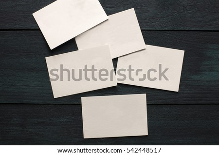 A photo of blank white thick cardboard business cards on a dark wooden background texture. A mockup or a minimalist banner with copyspace