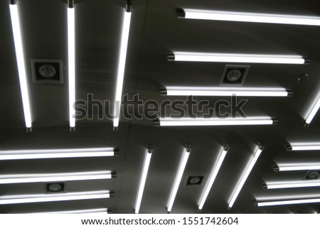 A photo of elongated thin tube fluorescent lamps arranged in a  geometric pattern on a dark background