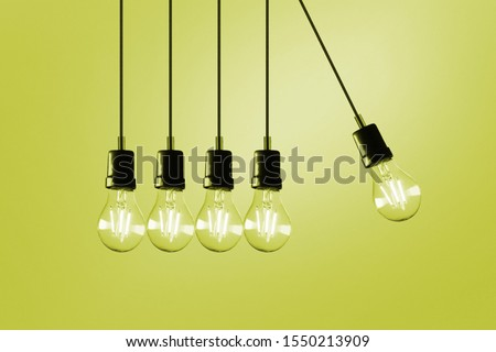 A photo of five lightbulbs hanging like pendulums in front of a yellow background  #1550213909