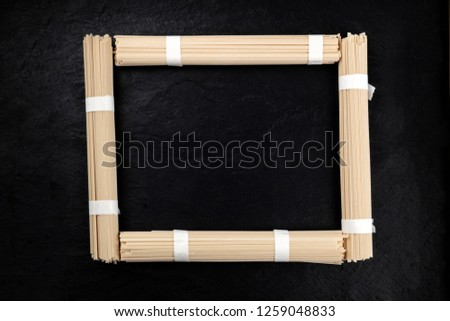 A photo of individually wrapped portions of udon noodles, shot from above, forming a frame on a black background with a place for text