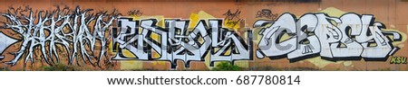 A photo of several graffiti artworks on the metal wall. Graffiti drawings are made with white paint with black outlines and have an orange background. Texture of wall with graffiti decoration #687780814