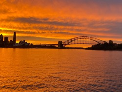 A photo of Sydney Harbour Bridge and city skyline during a radiant sunset which immediately followed a dramatic storm. Photo was taken from the water on the eastern side of the harbour in January 2021