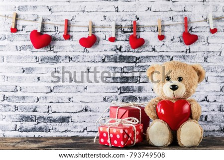 A photo of Teddy bear holding a heart-shaped balloon with red gift box and white brick wall background, Valentine concept #793749508