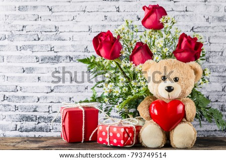 A photo of Teddy bear holding a heart-shaped balloon with red gift box and white brick wall background, Valentine concept #793749514