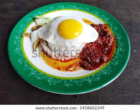 "A photo of the best ""nasi lemak sambal kerang telur mata"" in Kuala Lumpur. The food contain coconut rice, sunny egg, cockles sauce and fried anchovies."