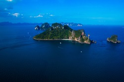 A photo of the Chicken Island in Krabi province Thailand, with boats and a beautiful sky.