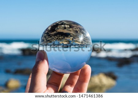 A photo of the ocean and rocks through a circular crystal ball turning the picture in the ball upside down. The picture in the ball is in focus and the background is out of focus.