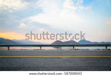A photo of the road near the dam with sunset scene