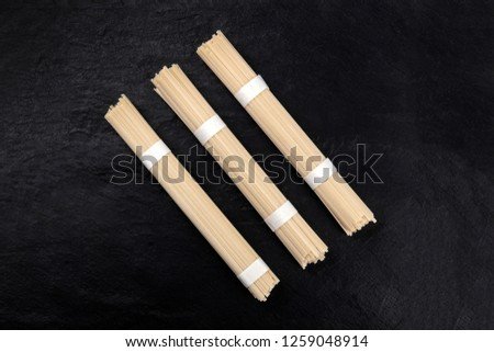 A photo of three individually wrapped portions of udon noodles, shot from the top on a black background with a place for text