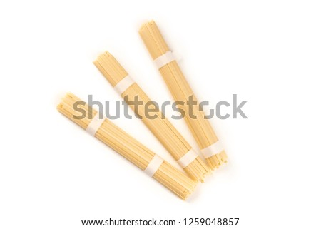 A photo of three individually wrapped portions of udon noodles, shot from the top on a white background with a place for text