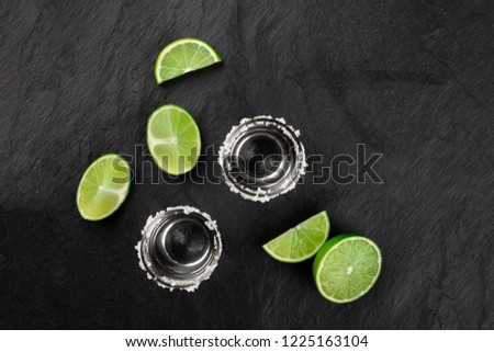 A photo of two tequila shots with lime slices, shot from the top on a black background with copy space #1225163104