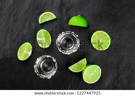 A photo of two tequila shots with many lime slices, shot from above on a black background with a place for text #1227447925