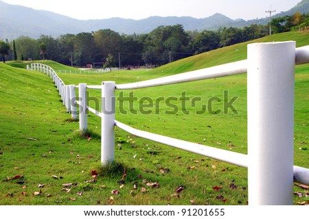 A photo of white fence on green hill side.