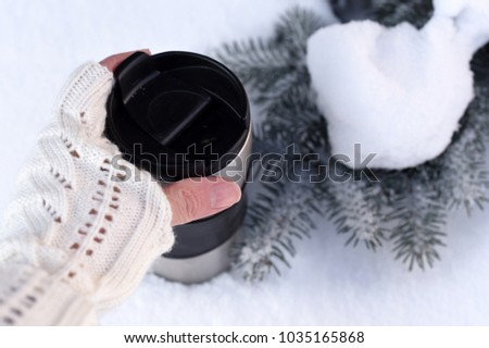 A photo with young woman's hand in a knitted mitten holding a cup of coffee against the winter snowy forest background   #1035165868