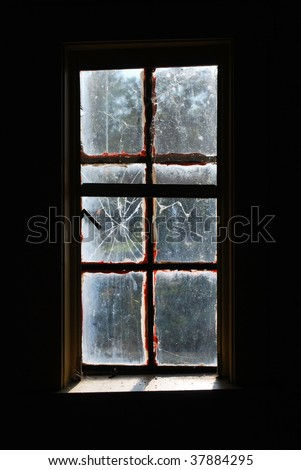 A photograph looking out of a dark broken glass window into the outside light.