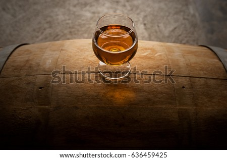 A photograph of a glass of whiskey sitting atop of a whiskey barrel. From above you can see the amber aromas from the whiskey and the groves and slits of the American white oak.