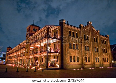 A photograph of a red brick building in Yokohama at night