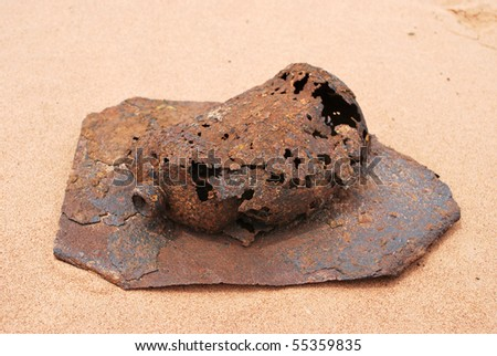 A photograph of a rusted metal container laying on a sheet of rusted metal in the sand.