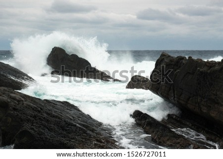 A photograph of a shoreline with waves breaking against the black jagged rocks. #1526727011