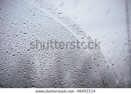 A photograph of rain drops on a vehicles front windshield.