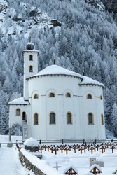 A photograph of Saas-Balen Church covered in snow in winter. Saas-Balen is a municipality in the district of Visp in the canton of Valais in Switzerland.