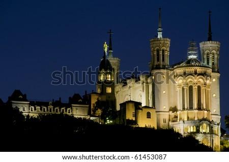 A photograph of the beautifully lit Basilique Notre Dame de fourvière in Lyon France, shot at dusk just after sundown