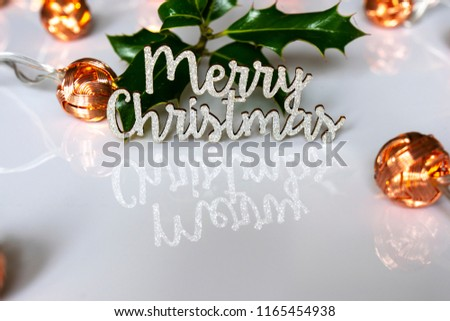 A photograph of the words Merry Christmas reflected in a white surface with holly and bronze lights  #1165454938