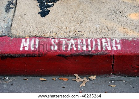 A photograph of the words No Standing painted on a city sidewalk curb.