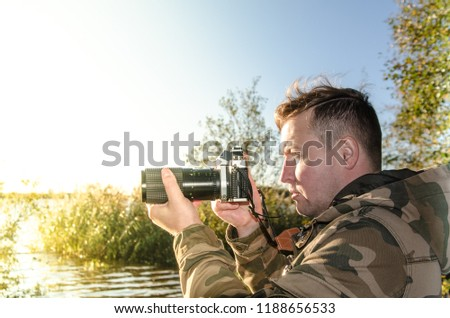A photographer dressed in camouflage jacket with film camera in his hands takes pictures on the shore of a lake or river. Portrait with yellow light leak.